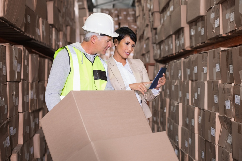Warehouse worker moving boxes on trolley talking to manager in a large warehouse.jpeg